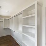 Closets are built out with painted shelving.