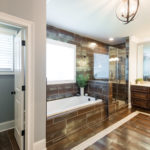 En suite master bathroom is so glamorous with metallic tile, whirlpool tub and glass shower.