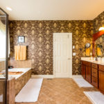 Double vanity, jacuzzi tub, glass and tile shower and a huge walk in closet complete this en suite bath.