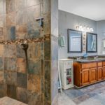 The earthy tones of the tiled shower blend harmoniously with the paint colors chosen by these homeowners.