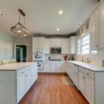 Spacious kitchen with gleaming hardwood, plenty of cabinet space and solid surface corian countertops.