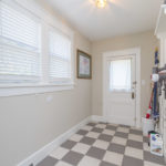 The utility/mud room with its cute checkered floor has utility connections and plenty of room. The original back door has storm door installed as well.