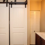 There is room for a full sized, side by side washer and dryer behind these cool barn doors.
