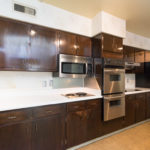 The kitchen has stainless appliances and solid surface countertops. There are so many cabinets in this kitchen for storage!