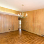 Paneled dining room in open great room with a great chandelier.