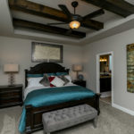 The master bedroom is on the main level and includes gorgeous wooden beams as an added architectural feature.