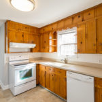 The larger of the two kitchens has solid surface countertops and white appliances.