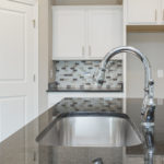 The granite countertops gleam and the sink fixtures shine!