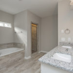 Luxurious master bath en suite with granite countertops, double vanity, large tub and separate shower.