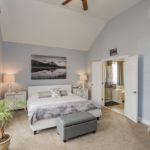 """Master bedroom on the main level also has vaulted ceiling and lots of window for a great """"escape"""" space from the busy world."""