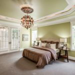 The spacious master bedroom with trey ceiling and french doors to screened porch is on the main level.
