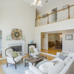 The cozy living room with soaring ceilings is located centrally in the house.