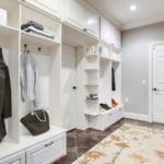 Headed to the basement area, here's your mud room with custom built cubbies. Directly behind the cubbies is a safe room with extra structural support & a steel door. (This photo has been virtually staged.)