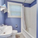The shared bathroom has a shower tub combo and a vanity sink.