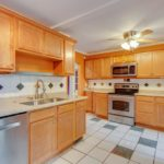The kitchen also features stainless steel appliances and a beautiful tile backsplash.