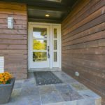 As you approach the front entrance, you can see that the walls have been wrapped in a beautiful stained wood siding, which gives this home a modern feel.