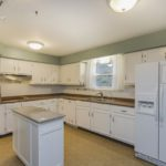 The kitchen has plenty of counter space, cabinet space and updated appliances including the refrigerator and electric cooktop. (Island does not remain).
