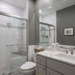 This renovated master bath has tile floor to ceiling, granite countertops, and lovely designer paint color.