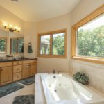 The master bathroom is filled with light. There is a double vanity with granite countertops and plenty of cabinet space.