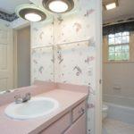 This full bath and cute pink cabinetry is shared by the two secondary bedrooms.