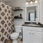 En suite bath for secondary bedroom also has granite countertops and combo tub/shower.