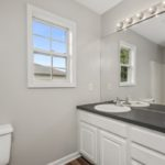 Single vanity in the primary bedroom and lots of light for getting ready for your day.