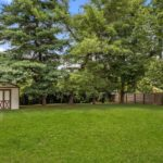The full back yard has a fence and a cute little storage shed for your convenience.